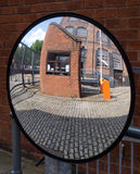 Security mirror. Convex security mirror reflecting security access entrance point Stock Photo