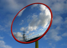 Security Mirror. Reflecting bright sky & electrical pylons in the distance stock photo