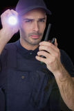 Security officer holding a torch and talking on walkie talkie Stock Photo