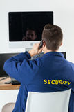 Security officer talking on telephone while looking at computer monitors. Rear view of security officer talking on telephone while looking at computer monitors Stock Photography