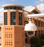 Video Security Camera Housing Mounted High on College Campus Royalty Free Stock Photo