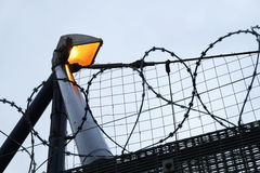 Security razor wire fence and lighting. Royalty Free Stock Photo