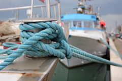 Security rope. A big boat moored to the dock with a blue safety rope Stock Photos