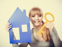 Young blonde lady holding symbols. Security safety home ownership concept. Young blonde lady holding symbols. Cheerful girl showing house key cutouts Royalty Free Stock Photo