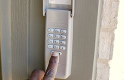 Security System Alarm Keypad. A person presses an outside home security keypad and garage opener royalty free stock photo