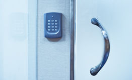 Security system on door. Electronic access control securing a modern glass door stock image