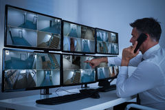 Security System Operator Looking At CCTV Footage. Side view of security system operator using walkie-talkie while looking at CCTV footage Royalty Free Stock Photography