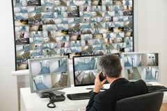 Security system operator looking at cctv footage. While Talking On Telephone Stock Photos