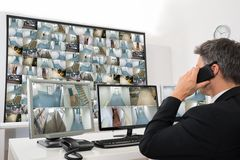 Security system operator looking at cctv footage. While Talking On Telephone Stock Image