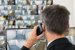 Security system operator looking at cctv footage. While Talking On Telephone Stock Photography