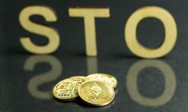 Security Token Offering STO sign with wooden letters and gold coins in front of it, Ethereum concept stock photography