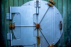 Security vault door on green wall Stock Photo