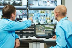Security video surveillance. Security executive chief discussing activity with worker in front of video monitoring surveillance security system Stock Image