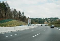 Security warning sign speed limit dangerous curve. Stuttgart, Germany - Mar 26, 2016: POV Driving fast on German autobahn highway on a clear spring day with royalty free stock photography