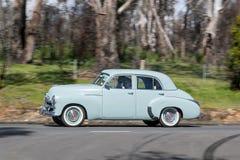 Sedán 1954 de Holden FJ que conduce en la carretera nacional foto de archivo