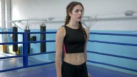 Sed que apaga, mujer atlética cansada que bebe el agua mineral durante el entrenamiento del deporte adentro dentro metrajes