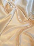Seda dourada com as pérolas como o fundo do casamento Fotografia de Stock