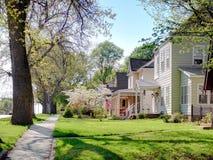 SEDALIA USA, APRIL 23 2015: Sikt på landsgatan med privata hus bland blomningträd och gräsmattor Amerikansk traditionell countr fotografering för bildbyråer