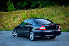 Sedan luxury black car parked in the parking lot near a forest. Left back corner. Cluj Napoca/Romania - August 27, 2017: Mercedes Benz C Class, model W203 - year Stock Photography