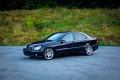 Sedan luxury black car parked in the parking lot near a forest. Left front corner. Cluj Napoca/Romania - August 27, 2017: Mercedes Benz C Class, model W203 Stock Photos
