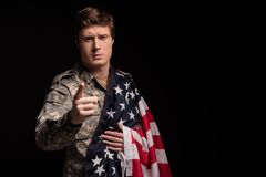 Sedate male soldier urging to protect the country. Waist up portrait of serious military guy looking at camera and pointing at it with upset look. USA Flag is Stock Photos