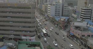 Sedd upptagen väg med övergående bilar, bussar, motorcyklister och gåfolk, imponerande skyskrapor, byggnader stock video