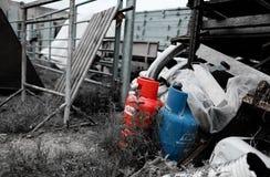 Sedda flaskor för komprimerad gas dumpade på en byggmästaregård och att visa den olika konstruktionshjälpmedel och apparaturen royaltyfri fotografi