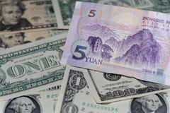 Sedel av yuanen för fem kines mot bakgrund av amerikanska dollar arkivbild