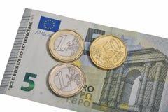 Sedel för euro fem med mynt som isoleras på den vita makroen Arkivbild
