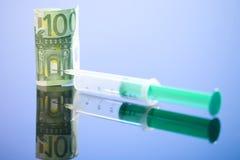 Sedel för euro 100 och injektionsspruta, slut upp Arkivbild