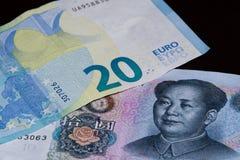 Sedel för euro tjugo ovanför yuan för tio kines på svart bakgrund royaltyfri fotografi