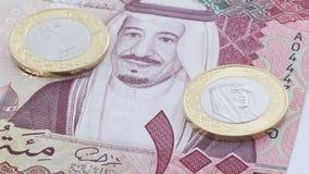 Sedel för saudierRiyal 100 och nytt mynt Arkivfoton