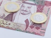 Sedel för saudierRiyal 100 och nytt mynt Arkivfoto
