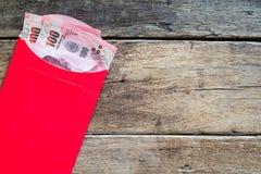 Sedel för thailändsk baht tvåhundra i rött kuvert som kinesiskt nytt y Royaltyfri Fotografi
