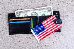 Sedel två dollar, svart handväska och en amerikanska flaggan Royaltyfri Foto