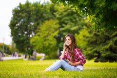 Sedendosi all'erba in parco Fotografia Stock