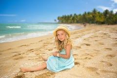 Sedendosi alla spiaggia Fotografia Stock