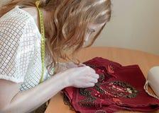 Sedendosi alla tavola e ricama la maglia rossa con le perle in studio fotografia stock