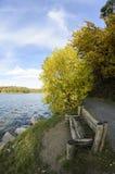 Sedendosi da un lago nei colori di autunno Fotografia Stock Libera da Diritti