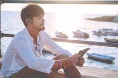 Sedendosi dalla compressa della lettura del mare in un pomeriggio soleggiato Immagine Stock Libera da Diritti