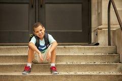 Sedendosi fuori della scuola Fotografia Stock