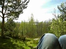 Sedendosi in natura pacifica che si rilassa e che esamina vista immagine stock
