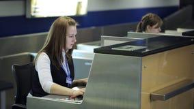 Sedendosi nell'area reception dell'aeroporto la donna sta funzionando con il computer video d archivio