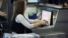 Sedendosi nell'area reception dell'aeroporto la donna sta funzionando con il documento della persona che dà il passaporto o la ca video d archivio