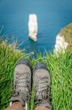 Sedendosi nell'erba con l'escursione delle scarpe Immagini Stock