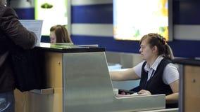 Sedendosi nella donna dell'aeroporto sta funzionando con il documento del cliente nell'area reception archivi video