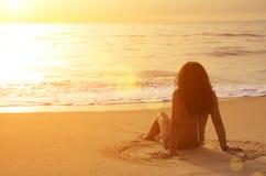 Sedendosi nella sabbia fotografia stock libera da diritti