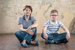 Sedendosi parallelamente sul pavimento Fotografia Stock