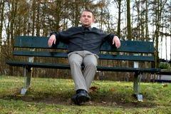 Sedendosi su un banco Fotografie Stock
