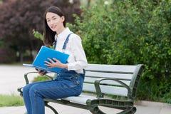 Sedendosi su un banco che legge un libro Immagine Stock Libera da Diritti